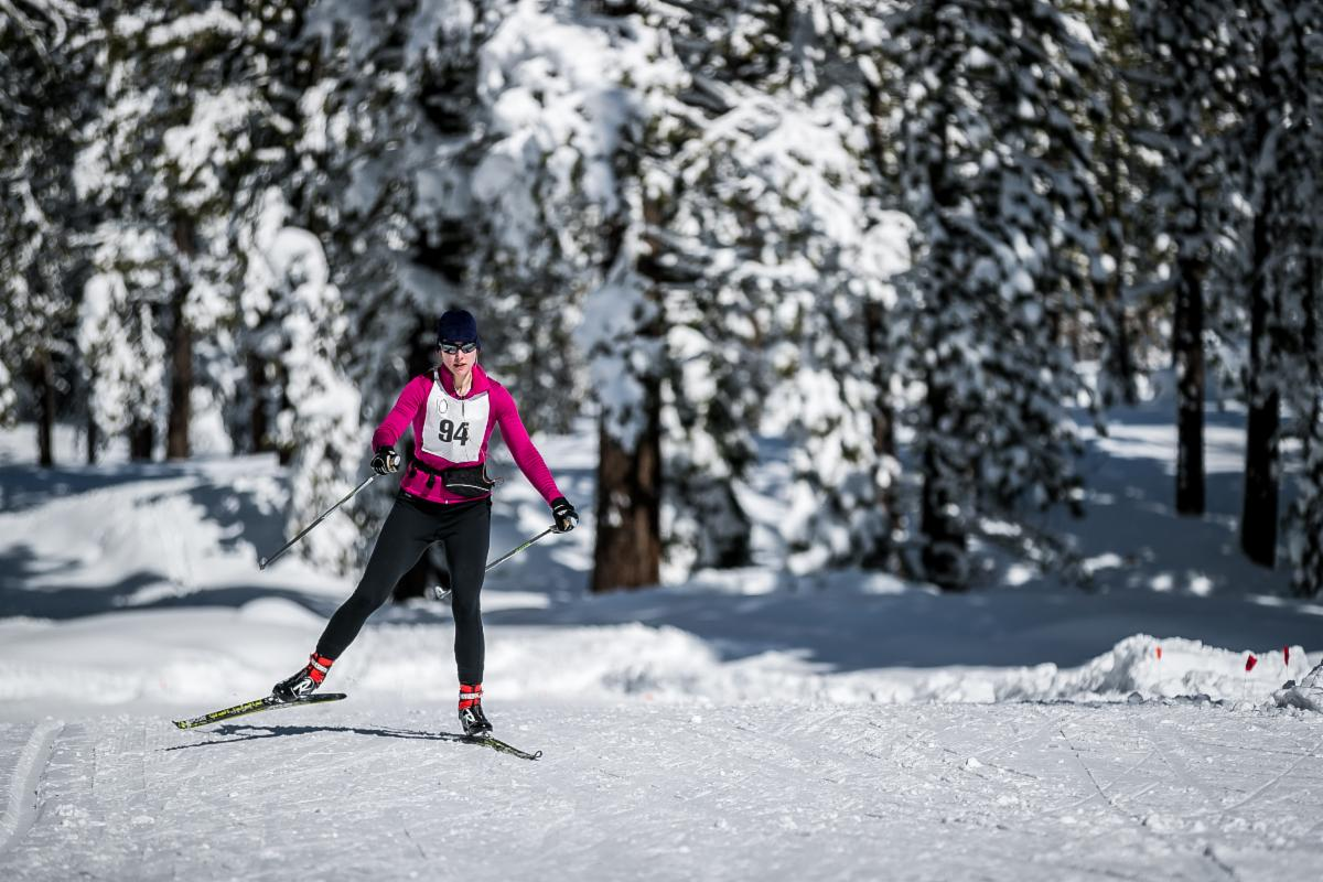 Woman in pink Nordic skiing with race bib.