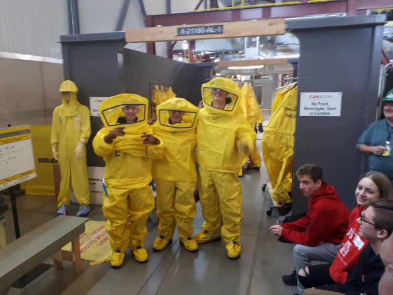 Male and female student wearing yellow hazmat suits as part of a tour of Ontario Power Generation plant.