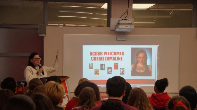 Female adult standing at a podium talking to a group of high school students about her book.