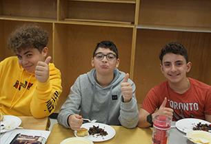 Three male students give three thumbs up to the Indigenous lunch