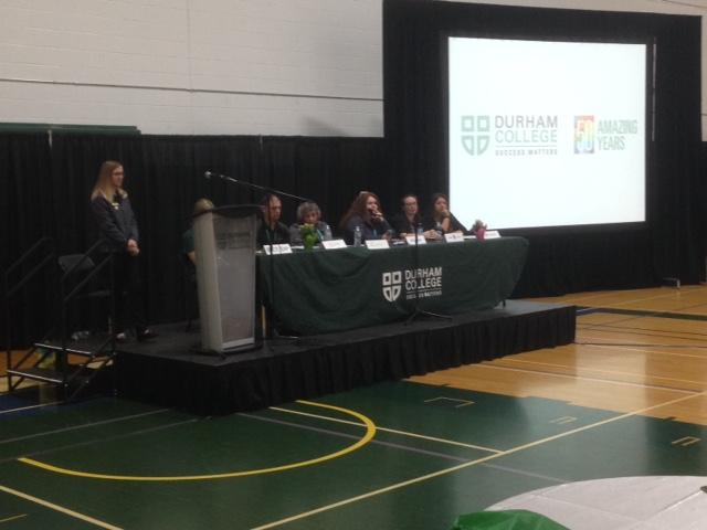 Female and male adults sitting at a table and standing at a podium at Durham College.