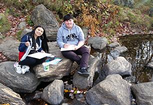 Students sitting on rocks and painting