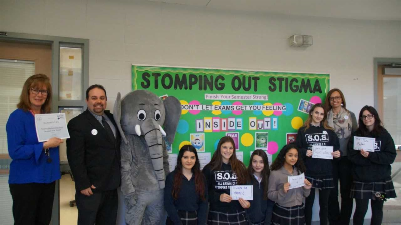 Female and male adults with female students standing in front of Stomping out Stigma bulletin board in school
