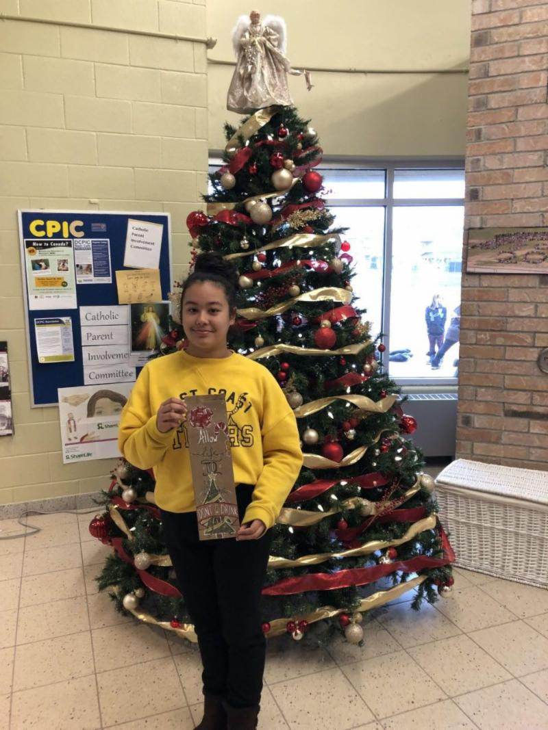 Female student holding her holiday LBCO bag design in front of Christmas tree
