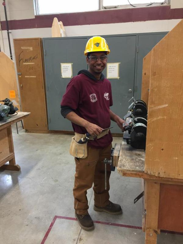male student wearing yellow hard hat and safety glass in a construction classroom smiling