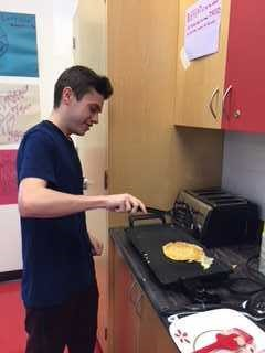 Male student making pancakes at school