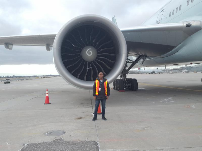 Male adult standing in front of an airplane engine
