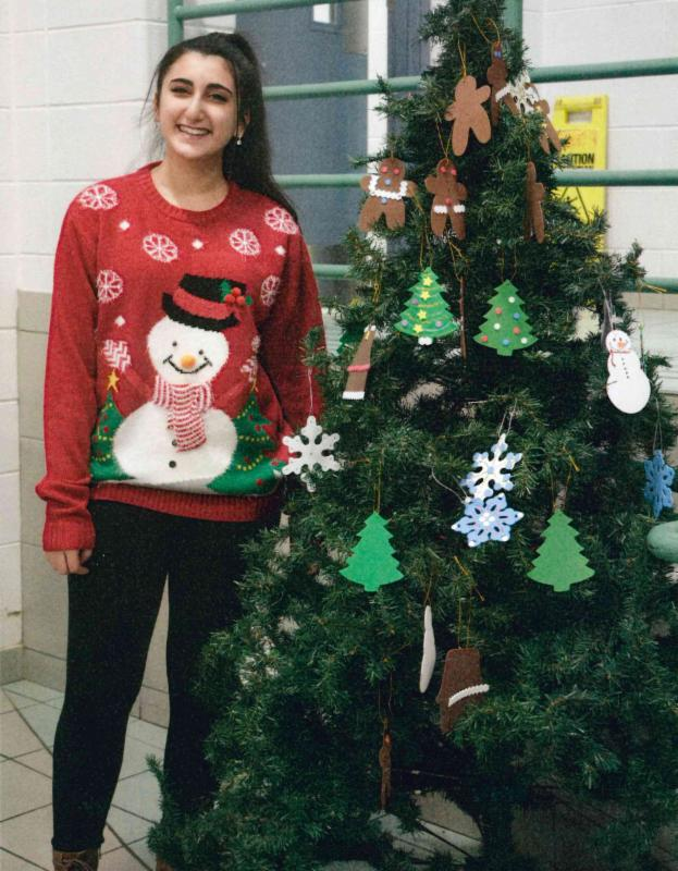 Female student wearing a snowman sweater standing beside a decorated Christmas tree.