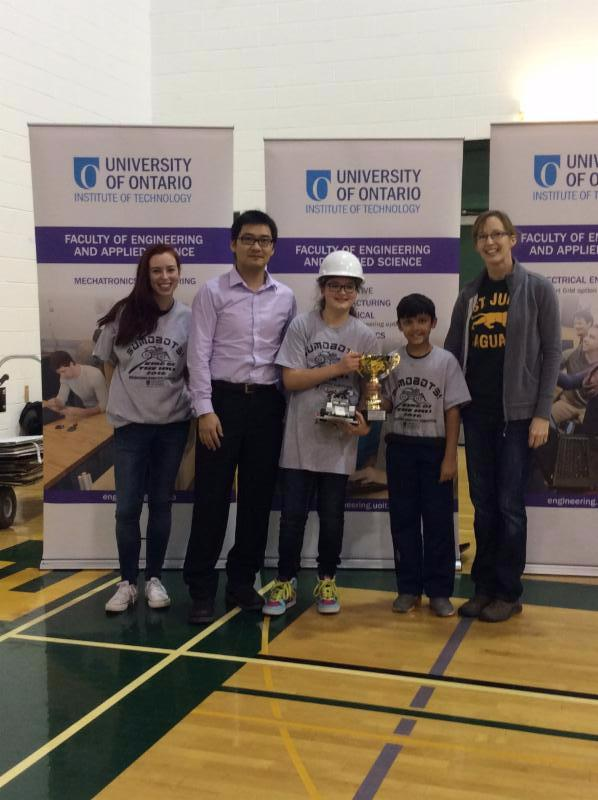 Female and male student receive best new school award from university robotics competition.
