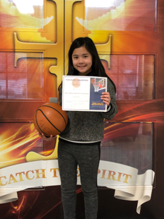 Female student holding certificate and basketball