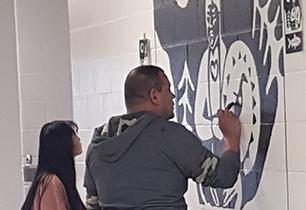 Female student working with male artist to paint the mural on a school wall.