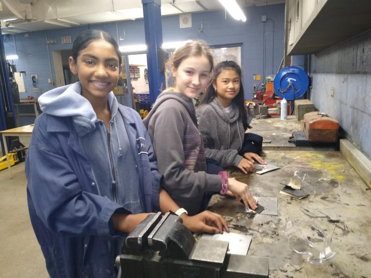 Three female students in a tech shop building a sign.