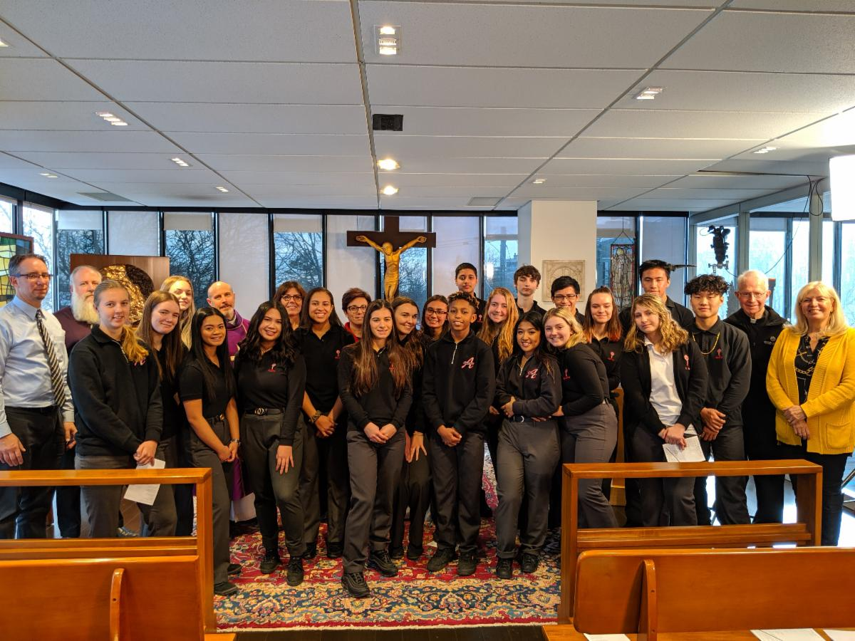 Group of male and female students with teachers and priest in a chapel at a television studio.