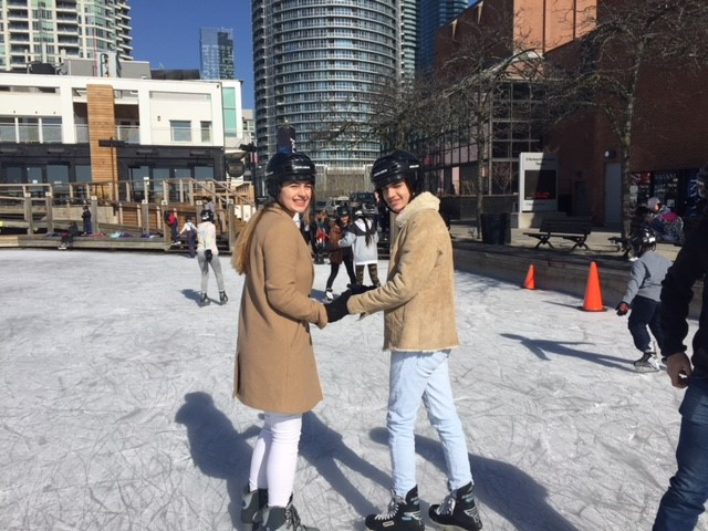 Female and male students skating outside on ice