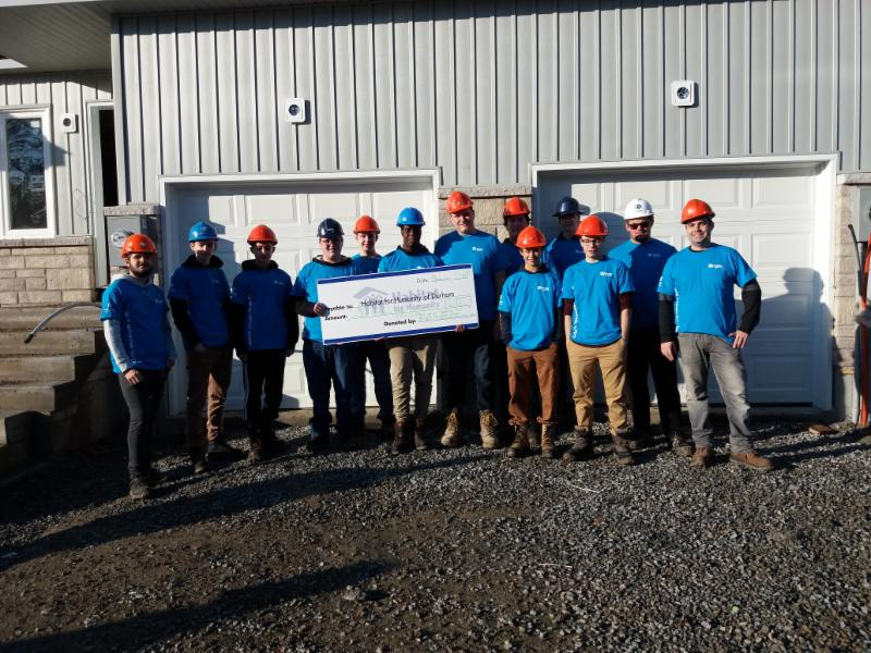 Construction students from Monsignor Paul Dwyer Catholic High School hold a large cheque for $2000 for Habitat for Humanity