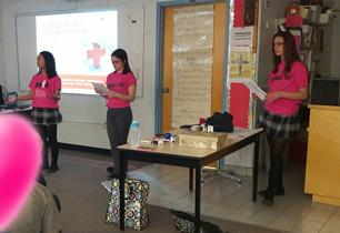 Three female students wearing pink t-shirts talk to students about the types of bullying
