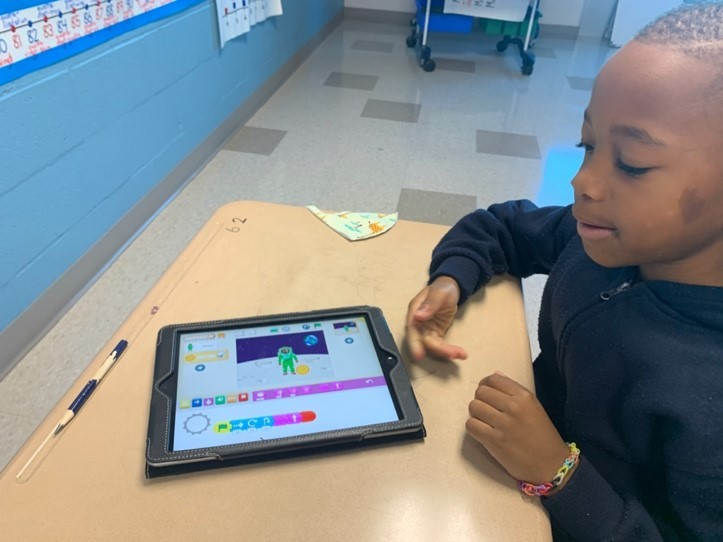 Male student coding on an iPad