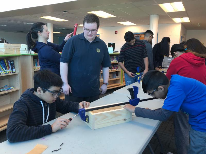 Male secondary student supporting two male students as they assemble a wooden box.