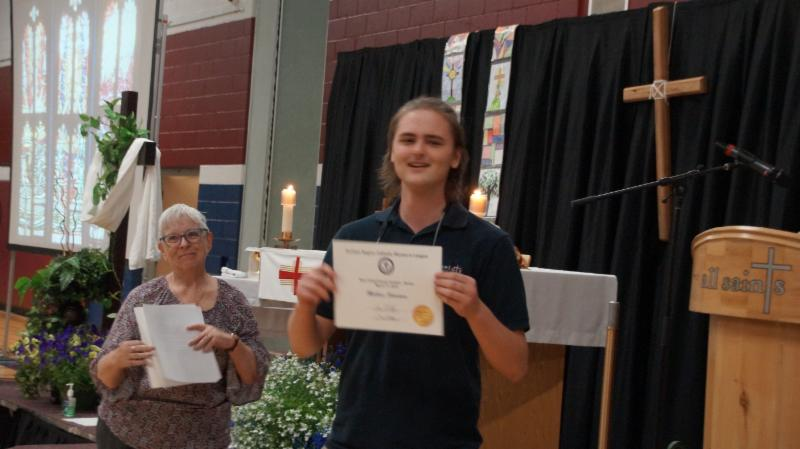 Male student holding a certificate for his essay