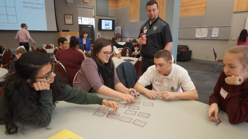 Female Math teacher and Math Coach plays a card game with three students