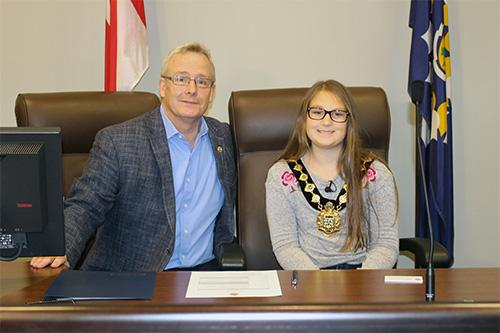 Male adult sitting with female student who is wearing of Mayor's office chain.