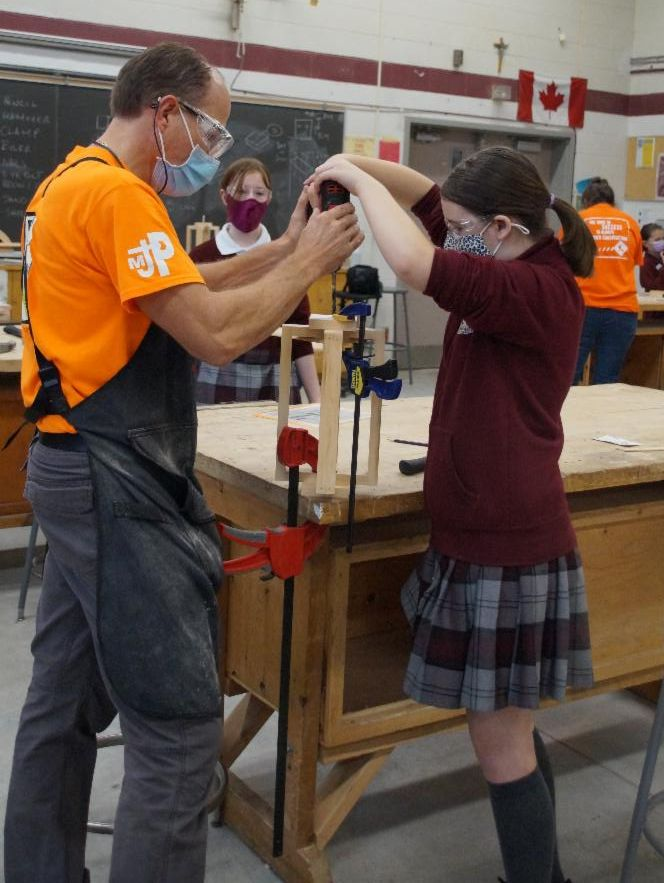 Male teacher helping female student to drill a hole into the top of the wooden lantern