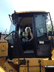 Female student sitting in a giant grader heavy equipment machinery.