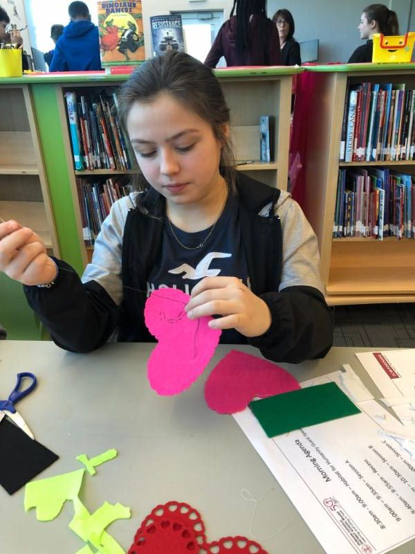 Female student sewing a heart shape pillow.