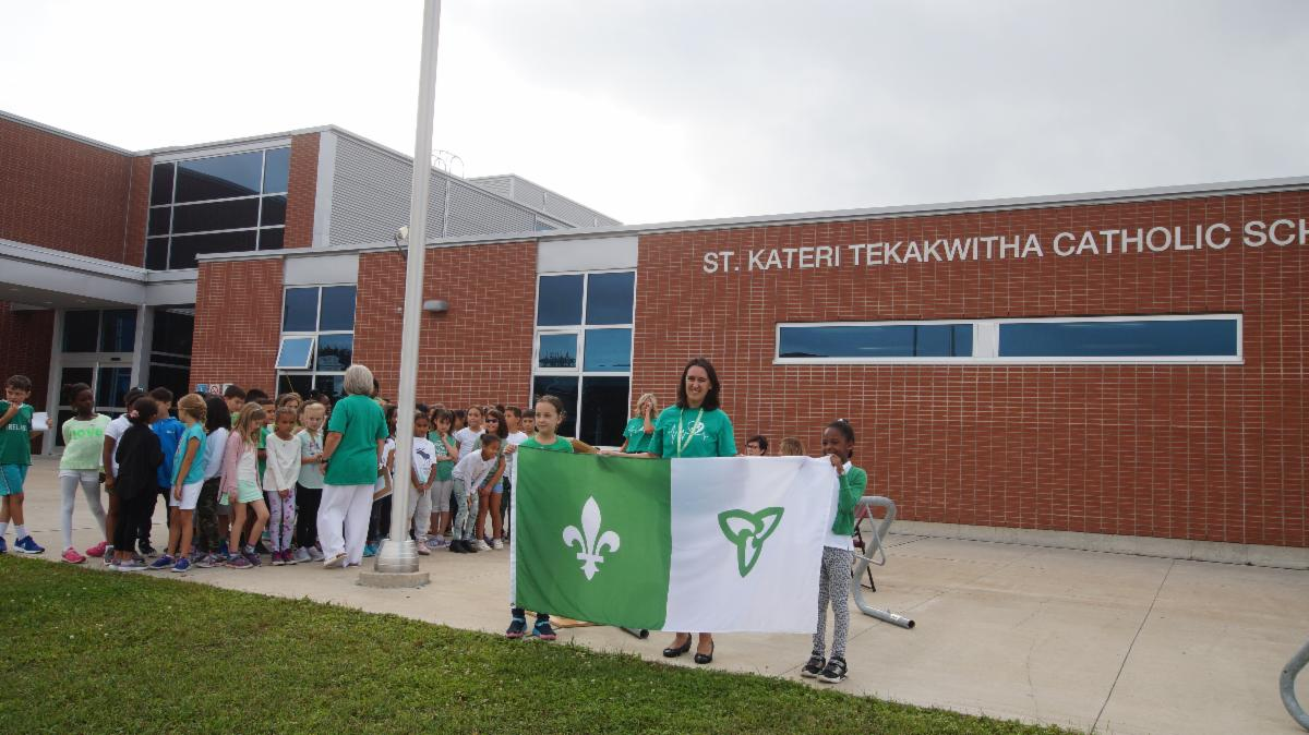 Two female students holding Franco-Ontario flag with female Principal