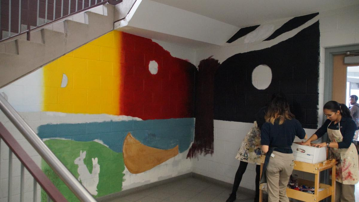 Three female students working on their Indigenous mural in the school's stairwell
