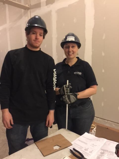 Male student working with a female electrician at a build site