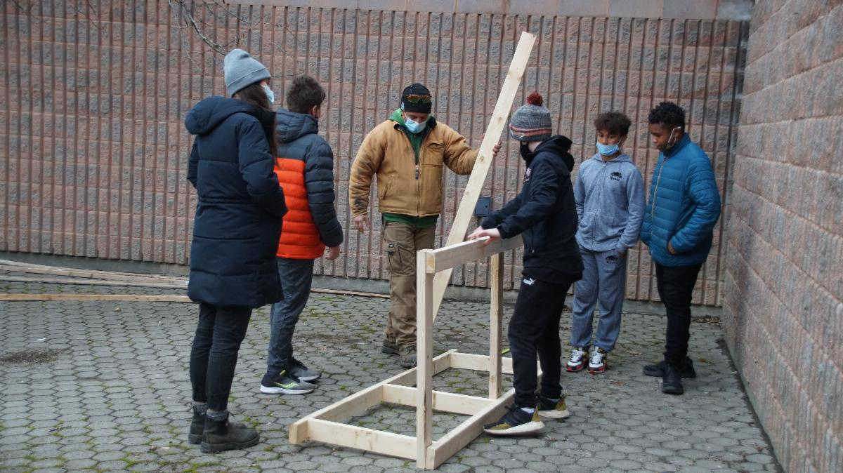Adult helping a group of students to build a bike rack.