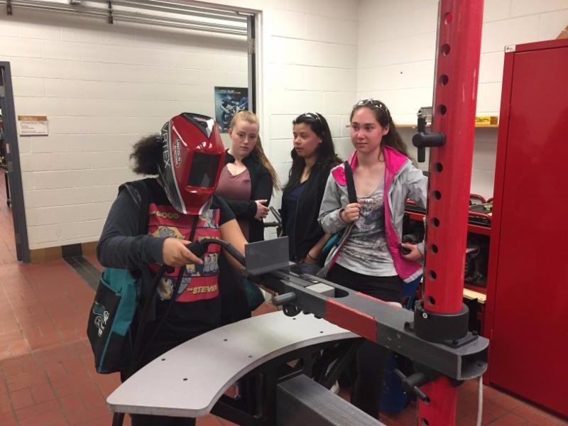 Female students welding in a classroom