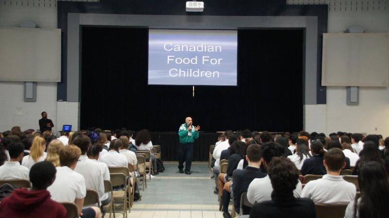 Dr. Simone talking to students at an assembly