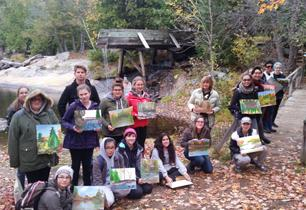 Male and female students outside holding their landscape oil paintings they have completed