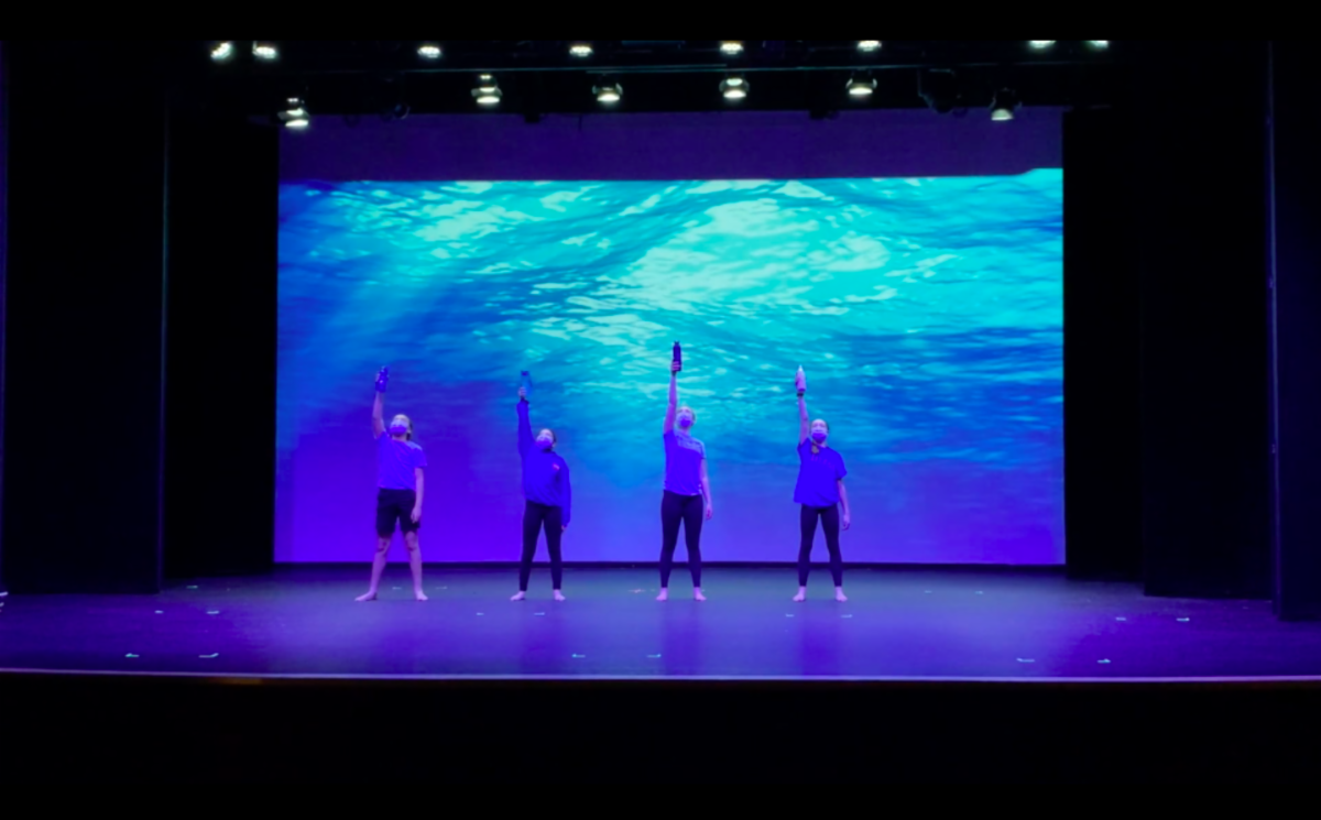 Four students onstage holding water bottles during dance