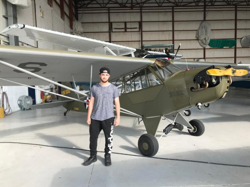 Male student standing beside an airplane