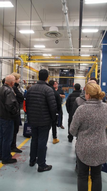 Parents and students listening to a college professor explain the Millwright program