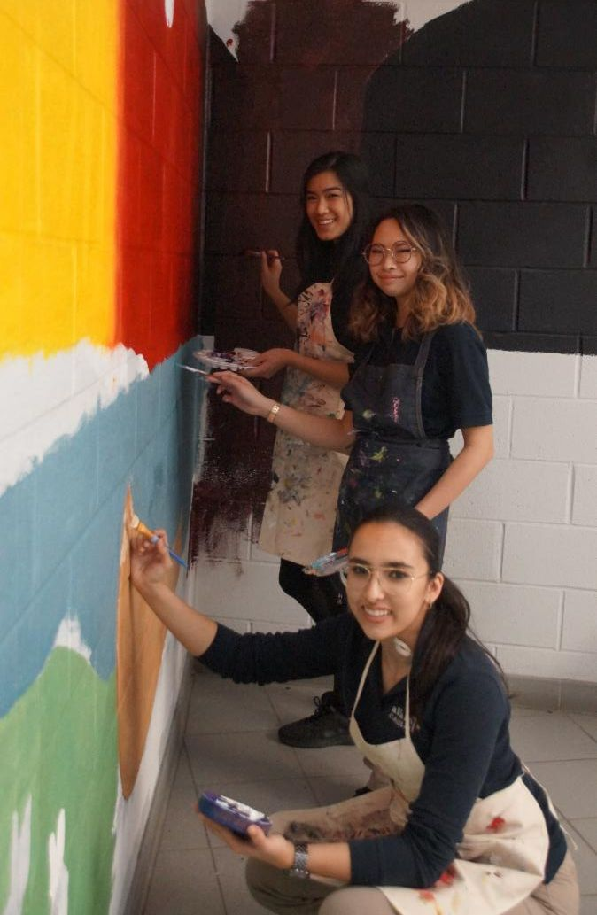 Three female students painting an Indigenous education mural in their school