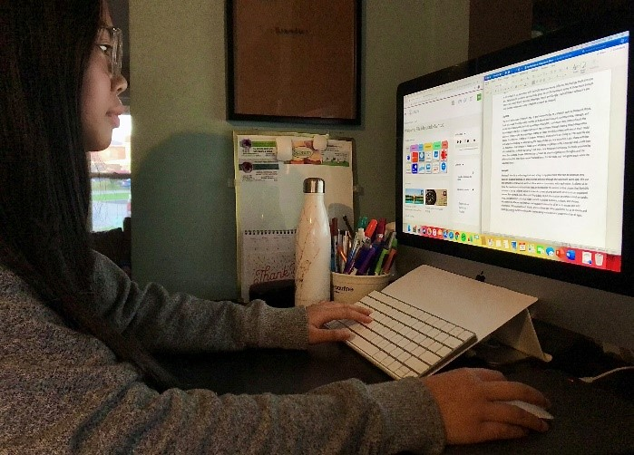 Female student looking at a computer screen and using Microsoft Word