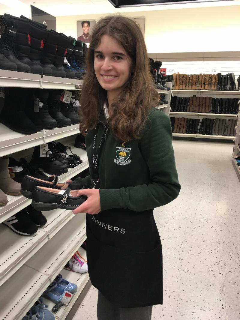 Female student wearing her school uniform and organizing shoes at a retail store.