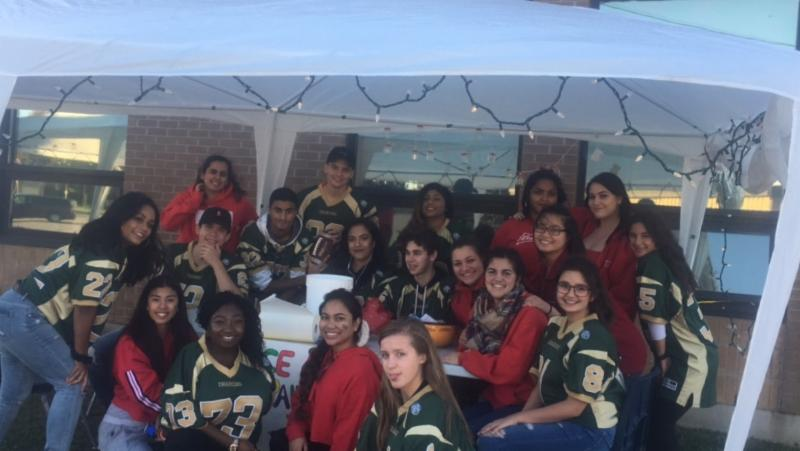 Students support the school's football team with a BBQ