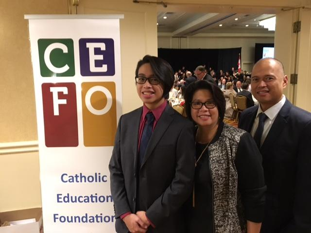 Male student standing with his mother and father by the Catholic Education Foundation of Ontario banner.