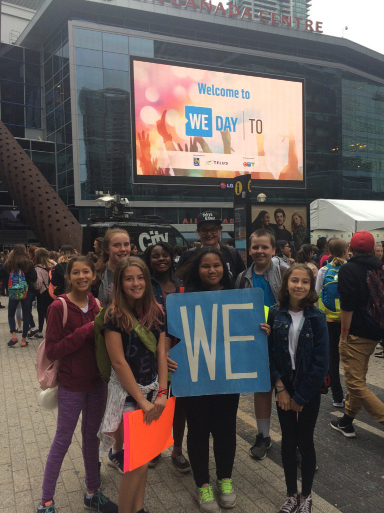 Students holding a WE sign outside of WE Day Toronto