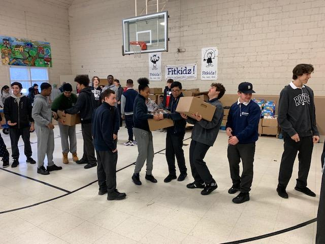 Students moving boxes of food out of a storage room.