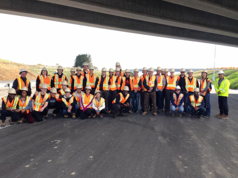 students wearing safety vests and hard hats pose for a picture under a highway overpass