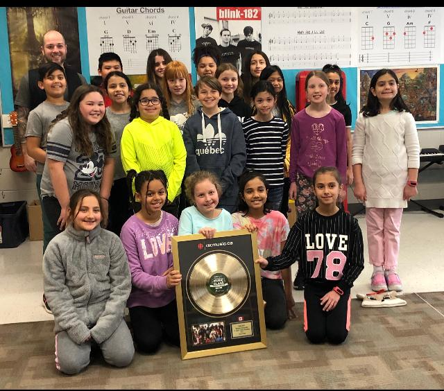 Group of male and female students with their male teacher holding their Gold record for their second place finish in a nation wide music classroom challenge.