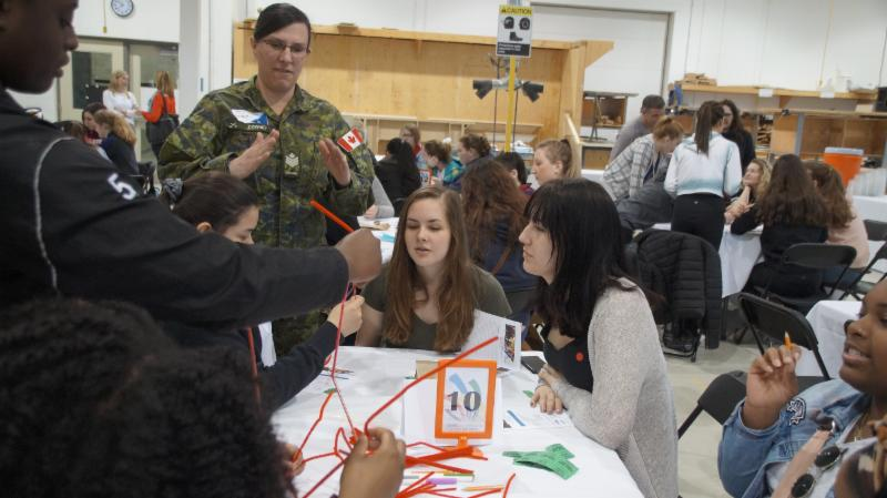 A table of female students working with a female mentor on how to build a free standing tower