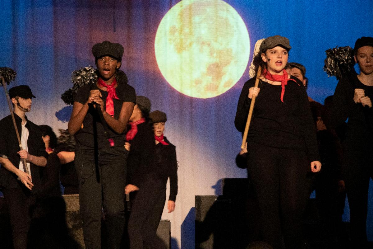 Female students singing on stage as Chimney Sweepers