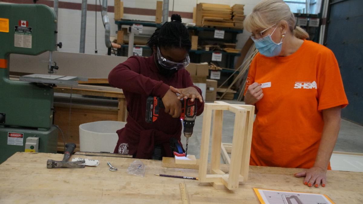 Female student drilling a hole in a piece of wood.